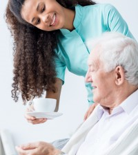 Caregiver giving senior man coffee